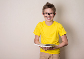 Health, education and people concept. Happy teen boy in braces and eyeglasses holding a book and laughing.