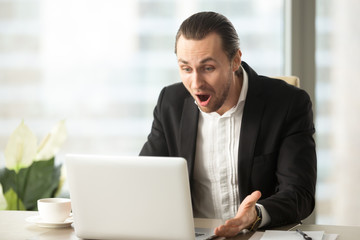 Frustrated young businessman looks at laptop screen screaming in anger at workplace in office. Unexpected high bill, unpaid debt, failing financial report, tax delinquency, breach of contract concept.
