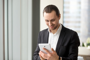 Young smiling handsome businessman looking at electronic tablet. Receiving good news, ordering food delivery, shopping online. Startup and entrepreneurship, financial success and investing concept.