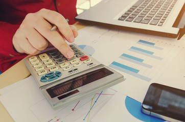young accountant or business man hand writing working finances and calculate with chart report, mobile smart phone and laptop computer on desk, home office, plan money cost saving, economy concept