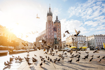 View on the central square and famous st. Marys basilica with pigeons flying during the sunrise in Krakow, Poland