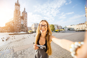 Young stylish woman tourist making selfie photo in front of the famous St. Mary's Basilica on the Market square during the sunrise in Krakow, Poland