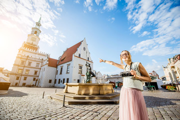 Porait of a young woman tourist traveling on the old Market sqaure in Poznan city during the morning light in Poland