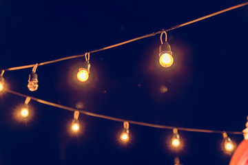 Selective focus on Light bulbs and  bokeh background with effect filter, Abstract background, vintage tone at night light festival. Fotomurales