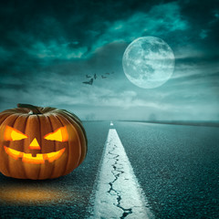 Spooky Halloween pumpkin on asphalt road at moonlight