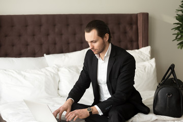 Young businessman sitting on bed beside luggage bag, working on laptop in hotel. Entrepreneur remotely works from hotel room while traveling. Business traveler finalizing work project, browsing web.