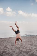 hombre en bañador haciendo el pino boca abajo en una playa