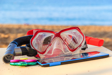 Mask for diving, a breathing tube, colored spinners and a tablet on a lounger on the beach and the sea. The concept of a summer off-season vacation of a teenager