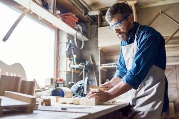 Bearded middle-aged craftsman wearing safety goggles and apron hammering nails into board, interior of messy workshop on background