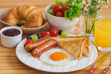 Homemade breakfast with sunny side up fried egg toast sausage fruits vegetable strawberry jam and orange juice in top view with copy space.Delicious homemade american breakfast concept for background