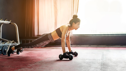 Asian sports woman doing exercises with dumbbell and push-ups at the gym