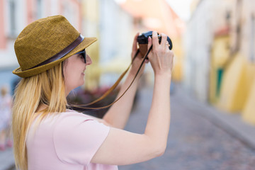 travel and photography concept - young woman tourist walking with camera
