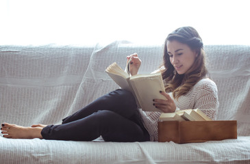 girl reading a book closeup on the sofa