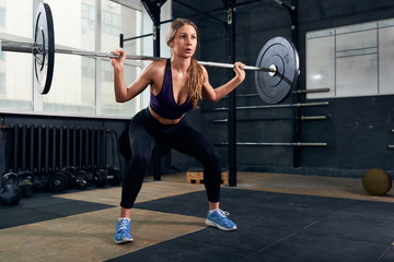 Portrait of strong young woman performing shoulder press with heavy barbell during cross fitness workout in modern gym