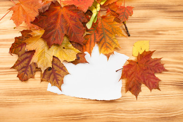 A piece of paper with autumn leaves on a wooden table