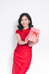 Pretty young glamorous asian woman dressed in red dress with a present