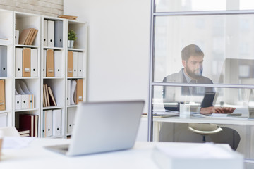 Background image of modern office space with desks and blurred businessman working behind glass wall, copy space