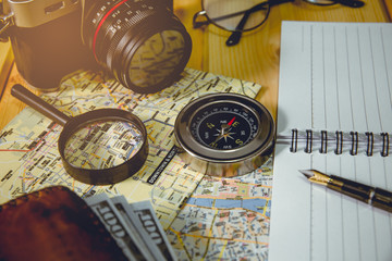 The compass is placed on a city map with objects nearby. Tone of photo is vintage style.