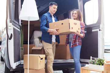 Portrait of smiling young man and woman unloading boxes and furniture from moving van outdoors