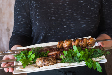 Waiter brings shish-kebab with grilled vegetables on white dish. Meat, field mushrooms and fresh green herbs, barbecue and natural food preparing in restaurant
