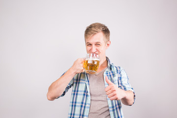 Happy young man holding beer mug and showing thumbs up