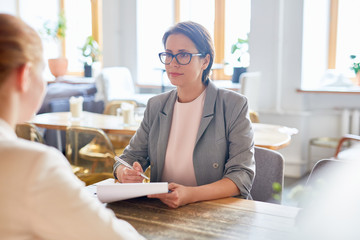 Confident emplolyer listening to applicant during interview in cafe