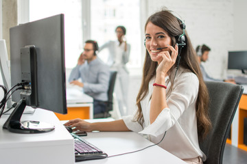 Young friendly operator woman agent with headsets working in a call centre.