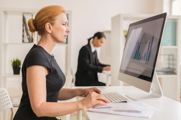 Financial analyst computing in front of monitor by her desk