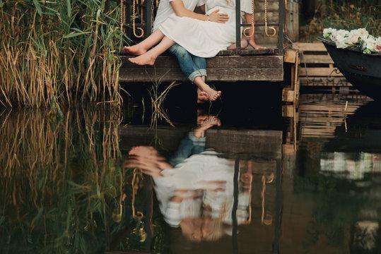 Молодой мужчина трогает живот своей беременной жены на мостике на берегу речки