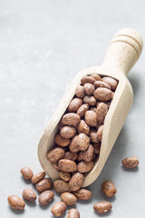 Uncooked dry pinto beans in a wooden scoop, copy space, vertical