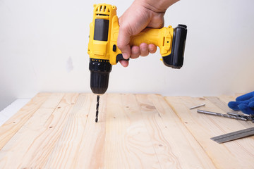 Craftsman working with power drill on wooden plank