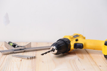 Close up yellow power drill on wooden. Do it your self concept.