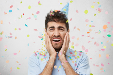 Picture of sociopathic young unshaven man in shirt screaming feeling terrified and unhappy as he can't stand noise and many people during birthday party. Negative human emotions and feelings