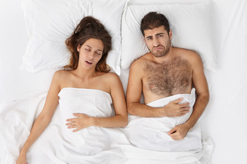 Indoor shot of brunette female takes nap with husband in comfortable hotel. Discontent fatigue male suffers from insomnia, has problem at work or home. Outraged man doesn`t want get up early