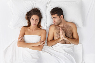 Young man wants lazy wife to cook breakfast after awake at dawn. Family couple have everyday problems, sort out srtong relationships in bedroom. Sorrorful male asks for forgiveness after betrayal