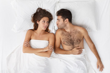 Top view of Caucasian family in bed before sleep: handsome sleepy man with bristle kissing good night his beautiful annoyed female with arms folded who is mad at him because he came home drunk again