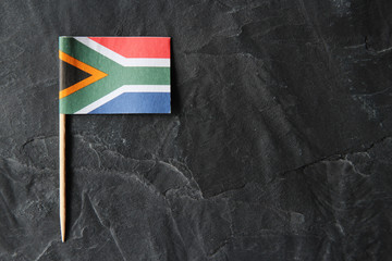 A South African flag toothpick on a black slate background. Wall mural