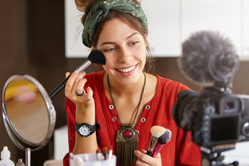 Camera taking photo of woman putting make up on her face, using cosmetic brushes. Beauty blogger woman taking video at home, telling tutorial speech about how to use and put powder correctly