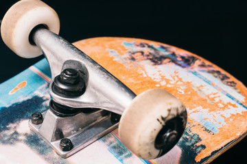 Skateboard parts on black background, rubbed deck and wheels on truck. Professional extreme sport and skateboarding elements, close up picture