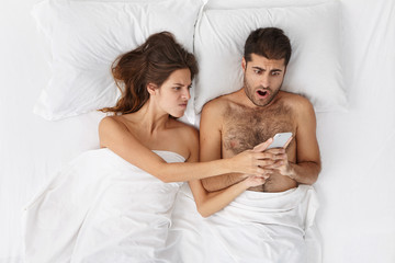 Irritated woman taking away cell phone from her obsessed internet addict boyfriend. Angry jealous wife snapping mobile out of her unfaithful husband hands, to check messages while feeling suspicious