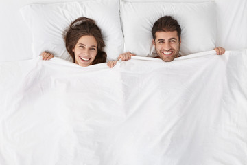Top view of heads of happy lovely couple lying in bed and smiling broadly after good sex. Lovers enjoying intimacy and togetherness. Just married spending first night at hotel room, feeling excited