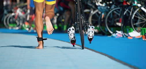 Triathlon bike the transition zone, the triathlonist runs on a bicycle