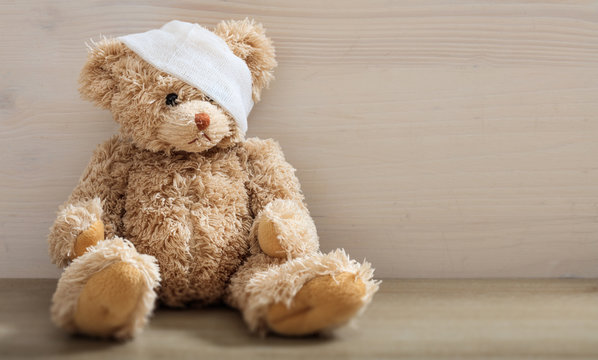 Teddy bear with bandage on a wooden floor
