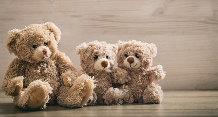 Teddy bears family sitting on a wooden background