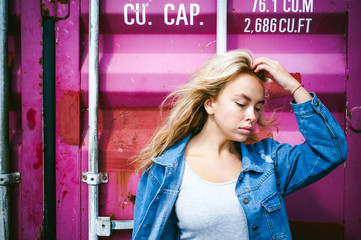young beautiful woman in jeans clothes outdoors. portrait of a girl with freckles on her face, stylish girl on a freight containers background, on a sunny summer day.