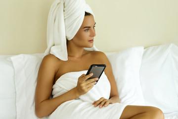 Woman using smartphone in bedroom