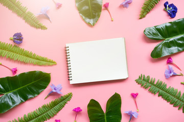 Flat lay design of blank notebook and leaves and flowers on the pink pastel background. with copy space