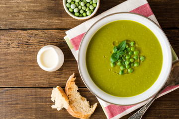 Green pea soup in bowl on wooden table