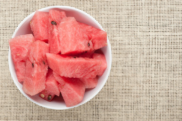 watermelon slices in plate on cloth textured background