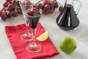 Homemade liqueur in glass and bottle with fresh grapes in background.